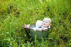 6 month old child photography. a water pail in the middle of a wildflower field + a baby = adorable!