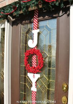 "Ribbon, letters, and a berry wreath combine for a festive front door shouting ""Joy!"" at visitors to your apartment."