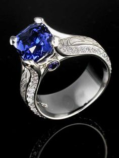 Juicy Liqueur Engagement RIng with a cushion cut sapphire center stone and diamond accents.