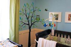 Our baby boy's owl themed nursery has an owl tree wall mural made with decals in the corner.