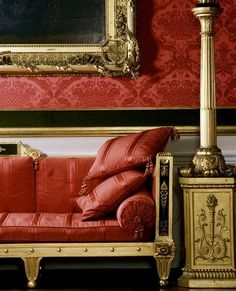 "A detail of the Regency period drawing room Southill Park, with bold in the Grecian taste sofas upholstered in red striped ""tabby"" now re-woven in Naples, and torchieres on plinths made by Marsh and Tatham. Photographer: Julian Nieman"