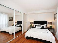 chambre à coucher avec grande armoire avec porte miroir coulissante encastrée dans le mur