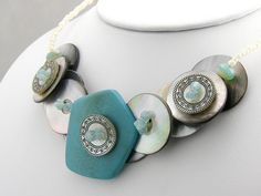 """$45  A beautiful mix of materials.  Mother of pearl buttons, layered with metal buttons.  A beautiful large focal button as a """"pendant"""" in the middle.  Then Swarovski crystals are sprinkled on top!  WOW."""