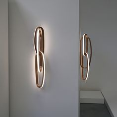 "These Niamh Barry sconces were inspired by her ""Fouette"" light sculpture. They are an interesting rethinking of available LED light technology recast in traditional materials. These sconces are comprised of three intertwined polished brass loops each of various sizes imbedded with LED lights. The word ""fouette"" refers to a series of fast turns that a ballet dancer makes."