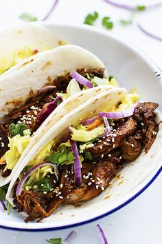 Juicy slow cooked shredded pork slathered in Korean bbq sauce, topped with creamy slaw, and wrapped in taco shells!