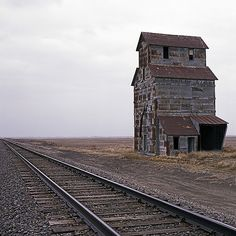 Abandoned grain elevator beside the tracks in a vast space of land....