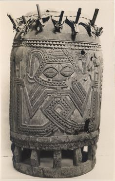 """Study of Yoruba drum """"for the Oshugbo society"""". Pattern of geometric figure with face and hands. Raised front base on small wooden pillars. Animal-skin [?] stretched and pegged across top. Plain backdrop. Medium: Gelatin silver print."""