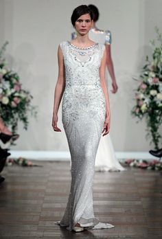 This Art Deco wedding gown by Jenny Packham has a net illusion neckline encrusted with crystals and beading, giving the appearance that the bride is wearing several ornate necklaces