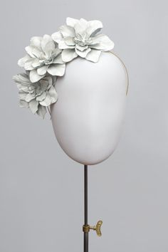 Manon is a striking headpiece consisting of three camellia flowers made from patent leather. https://www.etsy.com/uk/listing/280978394/flower-headpiece-white-leather-camellia