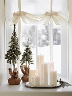 Simple & easy & elegant - white pillar candles, placed on a silver tray, add elegance to a windowsill. Two faux dwarf evergreens, wrapped in burlap, add a bit of color to the wintry scene.
