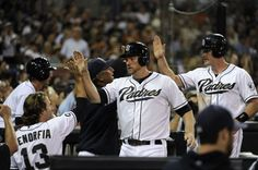 Game #113 8/7/12: Chase Headley #7 of the San Diego Padres and Logan Forsythe #11 are congratulated after scoring during the third inning of a baseball game against the Chicago Cubs at Petco Park on August 7, 2012 in San Diego, California. (Photo by Denis Poroy/Getty Images)