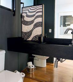 O lavabo costuma ser um dos menores ambientes da casa. Uma boa ideia é revestir uma parede com espelhos, que amplia o espaço, como no projeto do escritório Arqdonini