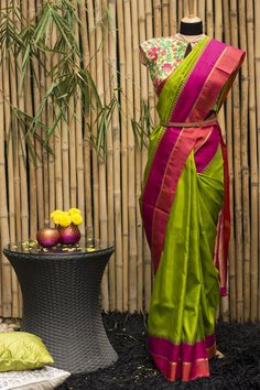 this number is bright green with a pink orange border and traditional temple motifs. With a beautifully lush golden orange pallu, this saree is such a spirit lifter. Paired with a brocade in orange or pink, this saree will steal the show every time. Blouse Patterns, Saree Blouse Designs, Traditional Sarees, Traditional Outfits, Indian Dresses, Indian Outfits, Parrot Green Saree, Lehenga Saree, Sari