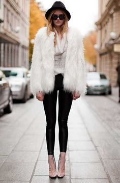 white fur Jacket.  Black pants Black Hat. Clear Shoes