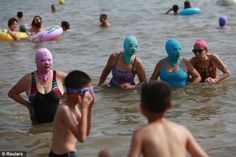Beach-goers in Qingdao are donning slightly scary nylon masks to protect themselves when they take to the sand