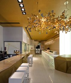 Sushicafé Avenida / Saraiva + Asociados. Love the gold ceiling and that light fittings!