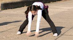 little girl doing exercises in park