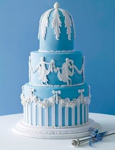 """Three tiers for this colonnaded cake! Fun fact: The gamboling goddesses were inspired by """"Dancing Hours,"""" one of Wedgwood's most famous designs. Cake covered with rolled fondant icing and decoration, $12 per slice, Cheryl Kleinman Cakes; 718-237-2271. Silverplate beaded cake knife, $25 for two-piece set (server not shown), Godinger Silver Art; godinger.com."""