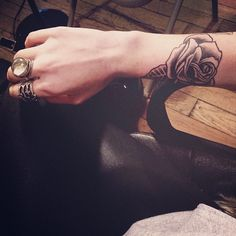Rose tattoo placed just above the wrist, lower arm.