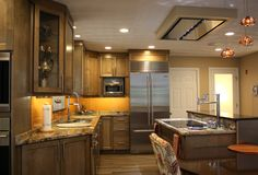 Transitional Kitchen- stainless steel appliances, induction cooktop, island seating at table height for 3, two sinks, bar sections with wine fridge, natural birch cabinets with black glaze, granite countertops