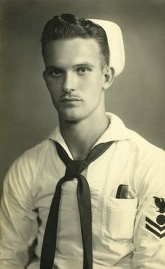 UNCOMFORTABLE YOUNG SAILOR POSITNG FOR A PORTAIT, COMB IN POCKET.