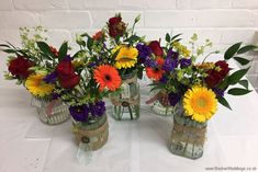 Bright and vibrant jam jar table centrepieces for the reception featuring roses, gerberas, lissianthus and alchamelia molis side view  Wedding Flowers Liverpool, Merseyside, Bridal Florist, Booker Flowers and Gifts, Booker Weddings