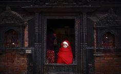 Menina olha para lado de fora de porta de entrada de templo no Nepal.