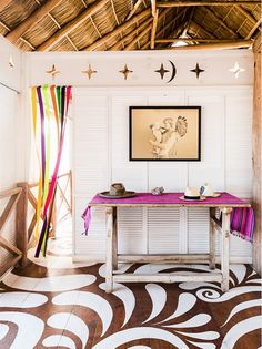 Airy space with white and wood decor, including hardwood floors with white design, and bright textiles and streamers.