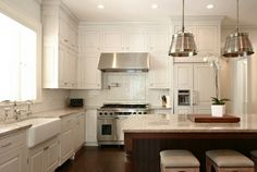 kitchens - Sloane Street Shop Light Polished White Cloud Granite countertops brushed nickel drum kitchen island pendants nailhead trim line upholstered chic stools white kitchen cabinets coffee stained kitchen island farmhouse sink pot filler subway tiles backsplash chevron herringbone pattern