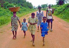 Depois da escola, uma família Ashanti caminha para trabalhar nos campos de milho perto de Adukrom, uma aldeia perto de Kumasi, em Gana. O pai leva uma espingarda para o caso de surgir alguma caça que lhes sirva de refeição. A cesta na cabeça de uma das meninas contém facões.   Fotografia: Victor Englebert.