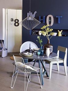 Dining room with blue wall + different letters and small round dinner table with different chairs