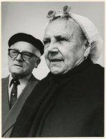 Scheveningse vrouw in klederdracht met echtgenoot, zij draagt een geplooide muts, een ijzer met boeken en parelspelden. ca 1960 Simon E. Smit #ZuidHolland #Scheveningen