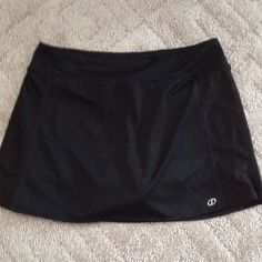 """Spaulding Black stretchy skort with detail. Polyester and spandex skort. Side panels have diagonal glittery detail and hem slits. Waistband is 2 1/4"""",  waist approx. 30"""", overall length is 14"""". Gently worn. Spalding Shorts Skorts"""