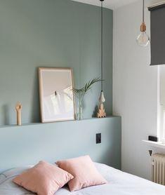 chambre scandinave avec des murs repeints en couleur vert de gris de teinte celadon, linge de lit blanc à petites rayures noires, coussins rose, suspensions originales