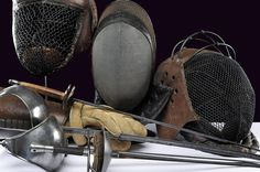 """A pair of sabres with rounded tip, blade with fuller marked """"Solingen"""", iron mounts; two foils, one with blade of square section, the other with triangular blade with hollow faces, both with flat, buttoned tip and iron mounts. Together with three masks with iron structure, metallic net and leather padding, and a fencing glove of stuffed and boiled leather."""
