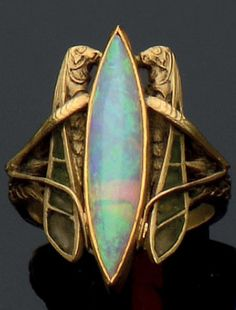 An Art Nouveau 18k gold, plique-à-jour enamel and opal ring, circa 1900. The ring centring a navette shaped opal, flanked by two grashoppers decorated with plique-à-jour enamel, the shoulders chiselled with ears of corn motif.