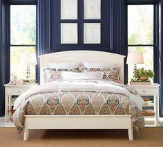 A dash of orange in this global-style duvet contrasts with the deep navy walls in this gorgeous bedroom.