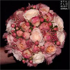 Stilren och elegant brudbukett i rosa toner, med rosor, hypericum och rosépeppar. Handbunden kompakt, med en undersida av fjädrar.
