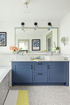 Traditional elements, such as marble hex tile underfoot and schoolhouse lights overhead, blend seamlessly with modern touches, like sleek faucets and angular vessel sinks in this bright bath.