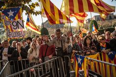 People wave Pro-Independence flags as they gather outside the Parliament of Catalonia during a parliamentary session to pass the start of the independence process on November 9, 2015 in Barcelona, Catalonia. The Catalan parliament voted and passed a motion declaring the start of secession process of Spain with 72 votes in favor and 63 votes against from unionists.