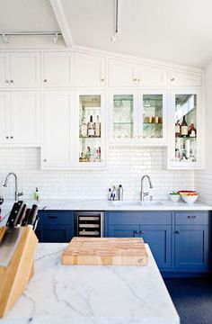White, open and airy kitchen with carra marble and blue painted cabinets