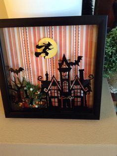Shadow box for Halloween . Haunted house cut from vinyl, attached to the inside glass. Using my Cricut Expressions