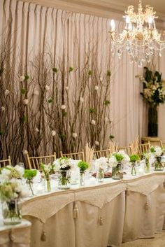 Tall branches with flowers sprinkled here and there as backdrop for the head table.