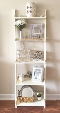 Shelf decor! Whites & neutrals. Adds dimension and life to a bland wall. Whole project costs under $70. Budget friendly! French, country, chic!!! Fake flowers and pretty frames do wonders. Thanks homegoods & Tuesday Morning!!! Paint color: Calico Cream Sherwin Williams.