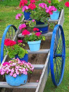 No jardim  E para você que assim como eu ama plantas, veja que linda esta floreira. Feita com um escada velha e rodas de bicicleta pintadas de azul, deram um charme extra a peça.
