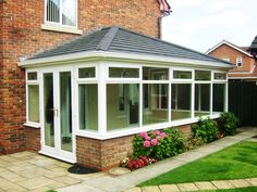 Large Supalite Roof, a Solid Tiled Conservatory Roof, with Charcoal Metrotiles, finished off with white guttering and installed on existing white UPVC Framework.