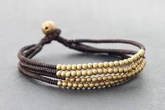 ♥100 % HAND WOVEN IN THAILAND This is hand woven bracelet made with dark brown cotton waxed cord weaved together brass beads . Closure using brass bell ♥ lightweight and comfortable to wear ♥ Bracelet measures 7.5 inch long ♥You can mix many of your favorite color for a slightly edgier