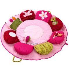 Ce tapis d'éveil fleur très moelleux présente un bouquet d'activités pour éveiller les sens des tout-petits : papier bruissant, pouët, grelot, miroir, jeu de cache-cache et de glisse...     Avec ses textures très variées, votre bébé développe le sens du toucher. Il se plie, se zippe et se transporte facilement grâce à ses 2 poignées.   Pratique, 2 poches à l'avant du tapis fermé permettent d'y glisser un biberon ou un lange.    Caractéristiques techniques :  Diam. : 90 cm. 9 activités…