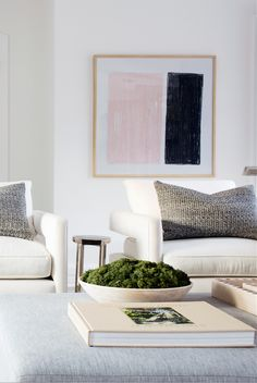 A modern pink and black color-blocked painting and bowl of moss add welcome pops of color and texture to this all-white living room.
