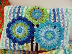 striped crochet pillow cover with crocheted flower appliques